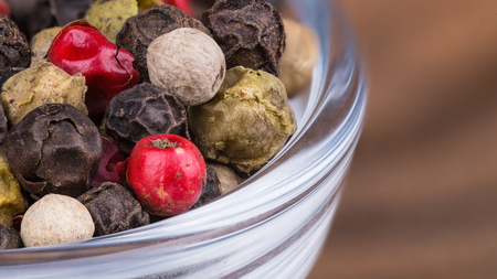 Close-up of different peppercorns in a bowl. Piper nigrum. Decorative colorful mixture of dried pepper corns in the glass with a blurred wood background. Stock Photo