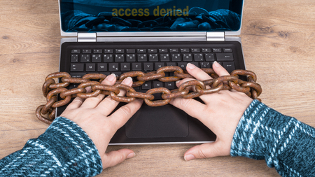 Close-up of hands, laptop keyboard and old rusty chains on wood background. Access denied. Idea of censorship, digitization, cyber security, backup, personal data and GDPR. Foto de archivo