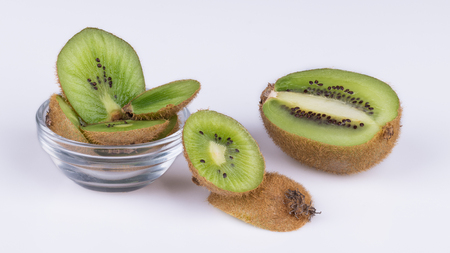 Sliced pieces of kiwis with brown skin. Actinidia deliciosa. Decorative green slices of sweet-sour kiwifruits in a glass bowl and laid on white background. Stock Photo