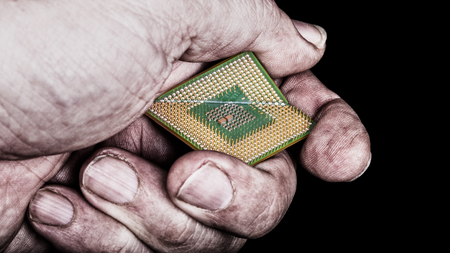 Dirty hand crushes microprocessor with critical bug. Broken computer chip in hackers fist on black background. Idea of cyber security, ICT, digitization and electronics industry.