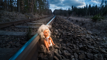 Train track with old doll lit by mystery light. Broken abandoned child toy at the rusty rail in dark forest. Idea of fate, apocalypse, sci-fi, war or abuse. Stock Photo