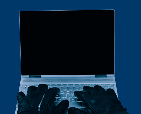 Laptop and hands in black leather gloves close-up. Copy space on dark display. Concept of hacking, espionage, censorship, sabotage, data protection, security, GDPR. Isolated on blue background.
