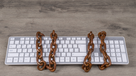 Computer keyboard tied with rusty chain. Old vintage chains on input device for digital informations. Concept of censorship, spy, cyber security, data protection, deletion or regulation, GDPR. Stok Fotoğraf