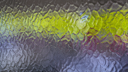 Background from a detail of opaque glass with a green horizontal strip. Close-up of bumpy grainy texture from frosted window pane with rough wavy relief pattern, color reflections and dim glow. 免版税图像 - 108803055