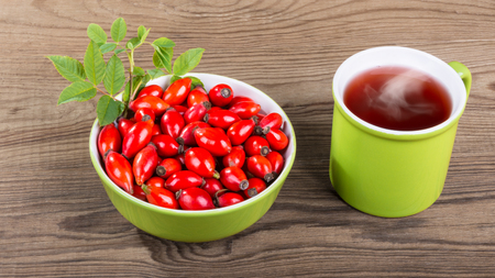 Rosehip tea and red briar fruit pile on brown wood background. Rosa canina. Ceramic mug with smoking medicinal drink. Beautiful bowl full of fresh ripe wild hips and decorative twig with green leaves. Stock Photo