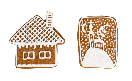 Traditional hand-painted Christmas gingerbreads. Two beautiful fragrant cookies decorated with sugar frosting. Cottage and chapel of aromatic sweets. Idea of Christmas, New Year, party. Isolated on white background. Stock Photo