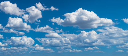 Romantic panoramic cloudscape with azure blue heaven. Idyllic sunlit panorama with flowing white fluffy clouds. Beautiful clear sky in background. Sunny summer day. Idea of climate, weather, ecology.