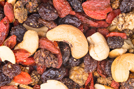 Mixture of cashew seeds and sweet dried berries close-up. Pile of roasted nuts, dry mulberries, raisins and goji fruits. Culinary background. Yummy vegetarian snack. Decorative brown-reddish texture. Stock Photo