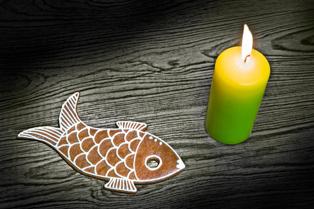 Gingerbread and burning candle. Christmas scene. Festive still life. Close up of cute sweet biscuit in fish shape. Dark wood background lit by wax light flame. Handmade cookie decorated with icing.