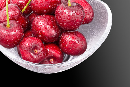 Detail of red sweet cherries in a bowl. Prunus avium. Beautiful pile of fresh ripe cherry fruit in wet glass dish. Water drops close-up. Healthy juicy dessert on black background. Full depth of field. Stock Photo