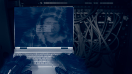Hacker with laptop on a dark background of structured cabling. Close-up of male hands in black gloves on keyboard, motion blur. Mysterious reflection of a spys head in hood on a digital display.