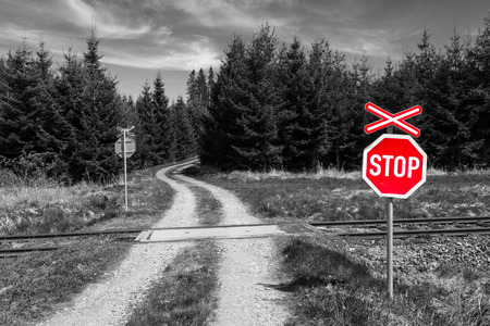 Stop sign on railroad crossing in nature. Red warning signal with crossbuck on black and white background with road through railroad and spruce forest. Intersection of railway line and off-road track.