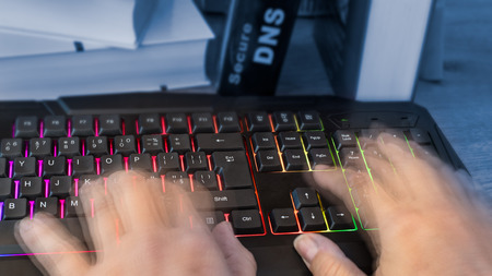 Colored computer keyboard with human hands in motion. Close-up of writing fingers of hacker, spy or censor. Detail of a book with Secure DNS lettering on background. Digitization and cyber security. Stock Photo