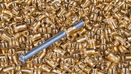 Steel bolt on texture from threaded inserts. Close-up of a single long silvery-blue screw with countersunk-head. Bronze thread bushings. Pile of glossy metal parts. Idea of supply, store or assembly.