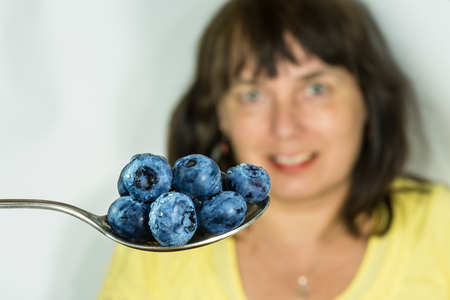Fresh juicy blueberries on a stainless teaspoon. Vaccinium myrtillus. Spoonful of blue bilberries close-up. Woman on blurred background. Sweet ripe berry fruit with water drops. Alternative medicine.