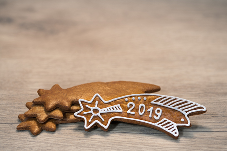 Still life with ornate New Year Bethlehem star on wood background. Handmade Xmas gingerbread cookie decorated by sugar icing laid on stacked golden sweet stars. For good luck in 2019. Selective focus.
