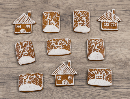 Group of ornate Christmas gingerbreads on a wood background. Beautiful gingerbread cookies in house shape and with hand-painted chapel in snow. Set of traditional Xmas sweets decorated by sugar icing.