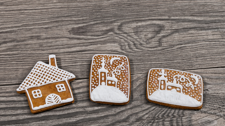 Traditional ornate Christmas gingerbreads on a wooden background. Decorative gingerbread pastries in house shape and with hand-painted chapel in snow. Beautiful aromatic baked sweets with sugar icing. Stock Photo