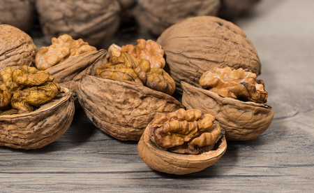 Group of partly peeled nuts with half shells closeup. Cracking of walnuts. Halves of cracked nutshells with nut meat on a wooden background. Delicious walnut kernels. Healthy vegetarian organic food.