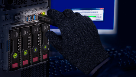 Hand in black glove holding USB flash drive. Computer data theft detail. Spy or saboteur is copying secret information from a server with dark hot-swap hard disks. Concept of cyber crime or espionage.