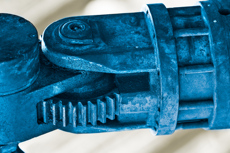 Hydraulic system detail with a gear wheel segment. Metal part of a building machine arm mechanism in blue on a white background. Engine joint close-up. Mechanical engineering, construction industry. Standard-Bild - 117351511