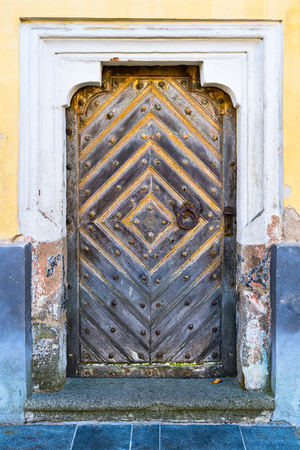 Baroque door in an old wall with decorative frame and a stone doorstep. Vintage entrance from solid wooden planks with a knocker and handle from rusty metal. Church in Cimelice, South Bohemia, Europe.