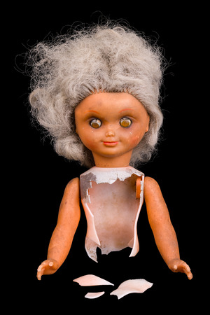 Old broken doll. Isolated on black background. Single damaged toy. Part of dirty child dolly. Gray hair and squint eyes. Plastic shards. Idea of childhood, fantasy, sci-fi or abuse, horror, halloween. Stockfoto