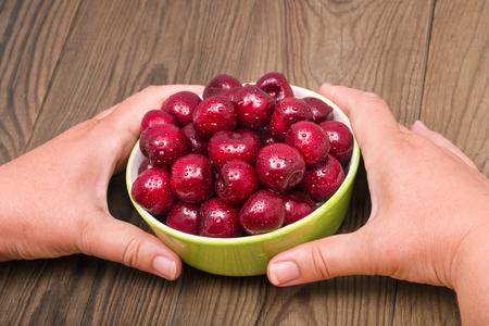 Sweet cherries pile. Green bowl. Human hands. Wood table. Prunus avium. Freshly picked wet red fruit. Ripe juicy berries in ceramic dish. Water drops. Natural rustic background. Vegan snack. Raw food.
