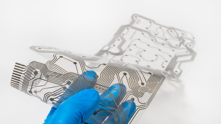 Flex printed circuit board. Hand in blue glove. White background. Transparent plastic membrane with brown copper layer PCB. Bending of patterned silicone sheet. Electronics industry. Selective focus.