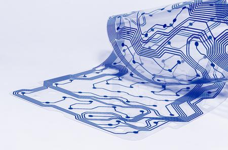 Elektronische flex-printplaat. Duidelijk membraan van gedemonteerd computertoetsenbord. Siliconen blad. PCB-detail opgerold tot een rol. Artistiek ontwerp. Abstracte gebogen plastic film. Blauw patroon. Witte achtergrond. Stockfoto