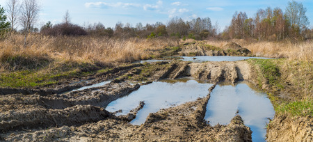 Off-road track. Tire imprints. Puddle detail. Military area. Impassable way. Muddy bumpy path in spring panoramic terrain. Bare trees, green bushes and dry grass in deserted rural landscape. Blue sky. 스톡 콘텐츠