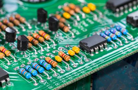 Composants electroniques. Circuits intégrés, résistances, transistors et condensateurs sur PCB. Détail du panneau de cuivre vert. Code couleur standard. Vieux matériel informatique. Electrotechnique. Tri des déchets. Éco.