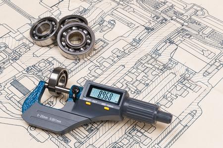 Micrometer screw gauge. Ball bearings. Drawing on background. Accurate measuring tool. Digital display. Round metal parts group. Engineering draft, plan, design. Education, study. Full depth of field. Stockfoto