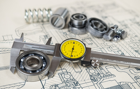 Accurate caliper gauge. Ball bearings diameter. Technical drafting. Analog metal measuring instrument with yellow round dial. Group of steel components on document. Machining concept. Selective focus.