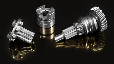 Metal machine parts. Cogwheel, grooved shaft. Artistic detail. Steel components of disassembled impact mechanism. Beautiful gold mirroring on shiny black background. Mechanical engineering, industry.