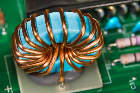 Enroulement de fil de cuivre. Détail de l'inducteur de l'onduleur. Pièces électroniques colorées. Belle bobine bleue en bloc d'alimentation électrique démonté. Gros plan du noyau de ferrite magnétique. Circuit imprimé vert. Électronique.