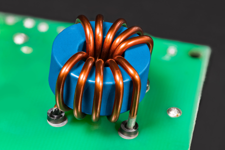 Blue inductor. Magnetic ferrite core detail. Open electric device. Induction coil with copper wire winding. Toroidal electronic part in green circuit board on black background. Electrical engineering. Banque d'images