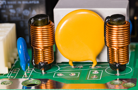 Varistance, inductances, condensateur et relais sur circuit imprimé vert. Bobines d'induction cylindriques avec noyau de ferrite, bobinage en fil de cuivre. Fond électro avec espace de copie sur la partie électronique ronde jaune.