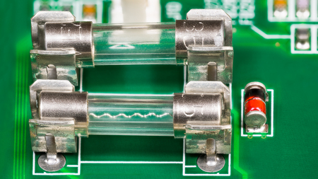 Miniature glass electric fuses detail with wavy fusible wire. Metal transparent current protector, red diode and blurry electronic components soldered on green circuit board. Electrical safety device. Banque d'images