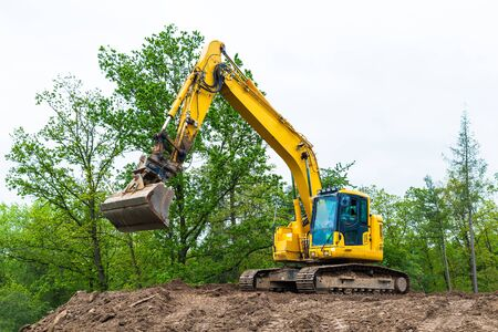 Yellow belt excavator on construction site. Hydraulic earth mover. Backhoe loader. Rotating operator cabin, shovel and continuous tracks. Pile of soil, spring sky, green tree tops. Building industry. 免版税图像
