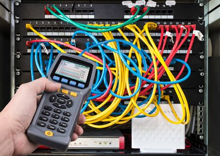Network test. Qualified cable performance tester in human hand detail. Data signal measurement. Colorful cables connected in patch panels of rack case. Working IT specialist. Professional maintenance.