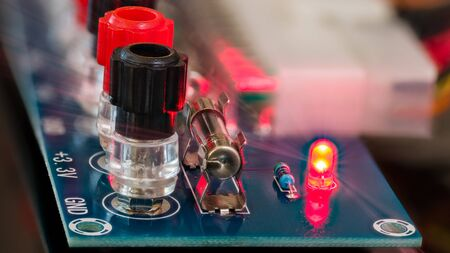 Power supply unit diagnostics. Electronic components detail on blue circuit board. Screw terminals, miniature fuse, shining red LED diode with light rays, resistor and blurred connector in background. Banque d'images