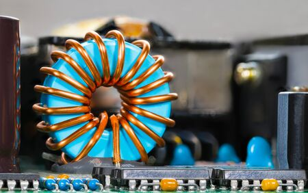 Blue coil core with copper wire winding and integrated circuits. Toroidal inductor detail and microchips. Electronic components on PCB. Dismantled inverter side view. Electrotechnics. Selective focus. Banque d'images