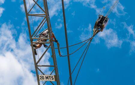 Instalación de grúa torre. Detalle del dispositivo de elevación. Trabaja en alturas. Hombre de trabajo en la pluma de acero de la máquina de elevación. Fondo de cielo azul. Trabajos de construcción peligrosos, aseguramiento. Seguridad Ocupacional. Vista inferior.
