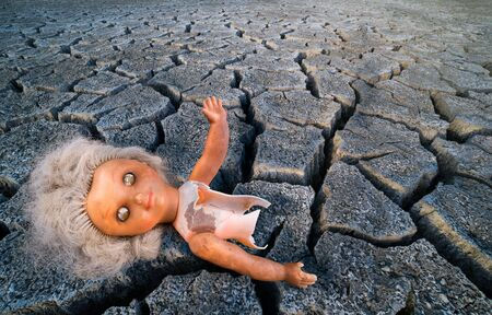 Abstract old plastic doll on dry scorched earth background. Damaged child toy on parched cracked ground. Dramatic detail. Drought, climate changes, ecological apocalypse or halloween and horror idea.