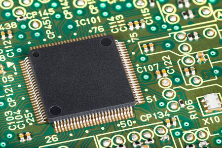 Close-up of integrated semiconductor microchip on circuit board. Surface-mount technology of electronic components. Black square micro chip on green electrotechnical texture. Computer hardware detail. Banque d'images