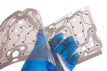 Plastic flex printed circuit board in a human palm isolated on white background. Hand of engineer in blue glove holding a bent membrane of dismantled computer keyboard with brown copper layer of PCB.