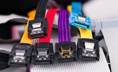 Internal serial connectors with colorful flat cables on pile of obsolete parallel cords. Computer bus interface for storage devices as hard, optical or solid-state disk drives. Data transfer hardware.