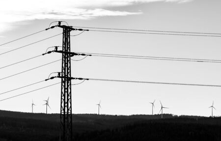Electric power transmission tower and group of wind turbines. Black and white silhouette. Electricity pylon and alternative renewable sources in landscape. Climatic change. Idea of sustainable energy. Stock Photo