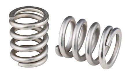 Two steel compression coil springs isolated on white background. Closeup of flexible shock absorbers with helical wire winding. Springy machine components. Elastic metal parts. Mechanical engineering. Reklamní fotografie